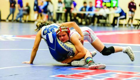 WRESTLED DOWN: Sophomore wrestler Olivia Moreno tackles a wrestler from a different school during a full-day tournament. Moreno has only been wrestling since her freshman year, opposing most of her family members.