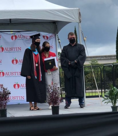 "Class of 2020 alumni Emma Davis (left) receives the cover of her high school diploma at the Class of 2020 ""Graduation Walk"" event alongside her mother and Bowie science teacher Jessica Davis (middle) and Principal Mark Robinson (right). Although she did enjoy the adapted graduation ceremony, Davis expressed her hope that more teachers are allowed to attend the ""Graduation Walk"" for the Class of 2021 as she believes it would make the event more enjoyable and personable."