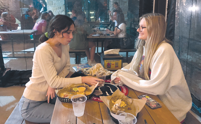 RAISING MONEY FOR LEUKEMIA: Juniors Ana Diaz (left) and Lilly Crosbie (right) eat Torchy's at a fundraising spirit night. Spirit nights held at Torchy's and Chipotle allowed students to donate to this cause.