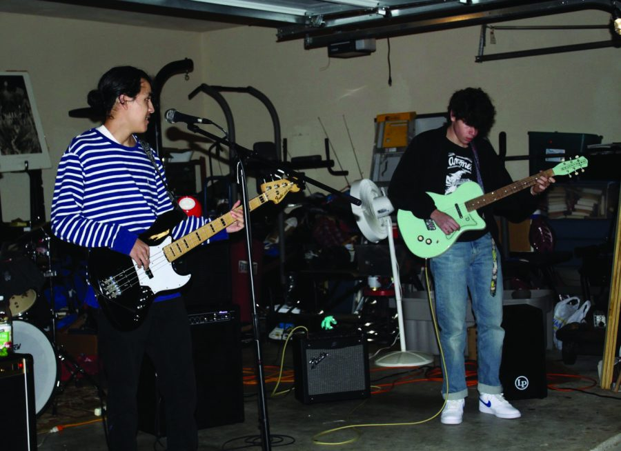PERFORMING LIVE :Senior Jack Lance (right) and Lucas Caballero (left) play along with the rest of the band infront of an audience of family and friends. Frog Town began practicing and performing together in October and plan to play together till the end of the school year.