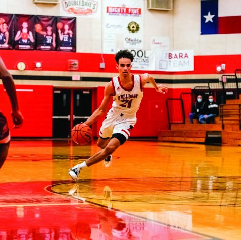 BREAK AWAY: Senior varsity power forward Cade Holzman has been playing basketball since he was four years old. He is pictured dribbling down the court in the game against Hays, where Bowie came away with a win of 66-59.