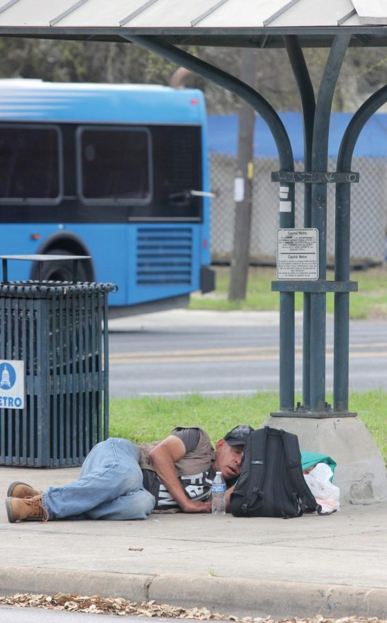 """WAITING FOR THE BUS: A man sleeps on the ground at a bus stop with his belongings beside him. Bus passes along with bottle water are some of the most commonly needed resources among homeless people. """"People need to get places and it's hard when you don't have money for lunch or transportation,"""" Sunrise Church volunteer coordinator Sarah Combs said. """"So then rather than giving them money I give them a bus pass, and then I personally also have business cards for Sunrise so that they know we have resources available to them if they want to use them."""""""