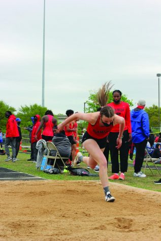 JUMPING FAR: Senior Abbey Smith completes a triple jump in the district track meet. Coach Benson specializes in coaching this event along with long jump and has helped these athletes place at this district meet.