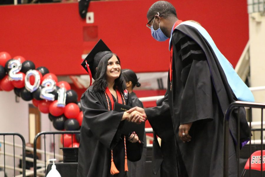 """SHAKING HANDS: Katie Martinez shakes the hand of AISD Chief Officer of Schools Dr. Anthony Mays. Martinez's orange cord represent her taking a college level course through UT OnRamps. """"I'm really glad I was part of so many amazing classes that give you a look into the real world,"""" Martinez said. """"I feel like those classes really shaped me into a better person and they prepared me for the world."""""""