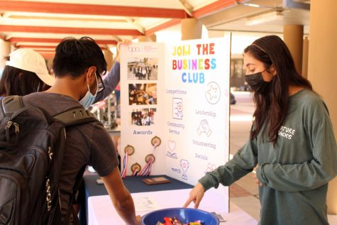 BUSINESS CLUB: Providing candy for new club members, Senior Zoya Faisal welcomes students to join her club.