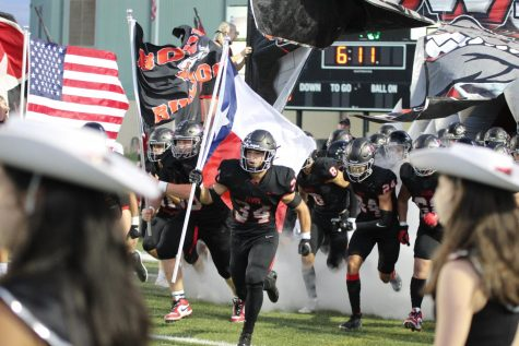 RUNNING DOWN THE FIELD: Senior Noah Camacho carries the Texas flag before the start of the homecoming game.